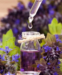 28440309 - spa background with violet flowers and glass vial with essential oil.